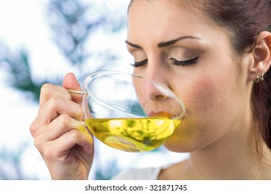 Beautiful woman drinking herbal tea with eyes closed