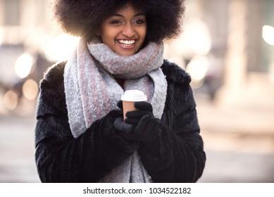 Beautiful woman drinking hot coffee - Afroamerican girl portrait outdoors
