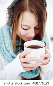 Beautiful woman drinking hot drink in winter park. Winter holidays concept. Close-up headshot. Selective Focus.