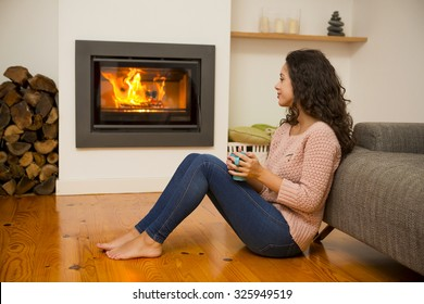 Beautiful woman drinking a hot tea at the warmth of the fireplace