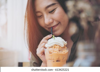 A beautiful woman drinking Thai tea milk shake and whipped cream on the top with straw in vintage cafe