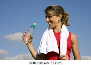 Beautiful woman drinking water after fitness
