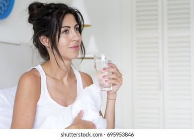 beautiful woman drinking  water in the bed at the morning.Healthy start of the day concept