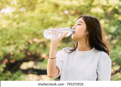 Beautiful woman drinking water at summer green park. Healthy lifestyle concept