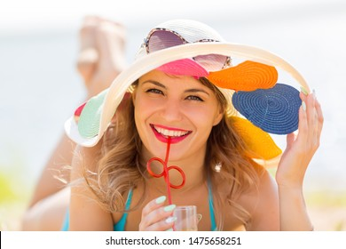 Beautiful woman drinks juice while lying on the beach. Brunette girl in a hat drinks juice through a straw while relaxing sunbathing on a beach.