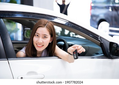 Beautiful woman driver holding keys her new car with smiling. Young woman with the keys at the car. Concept of having a new car.