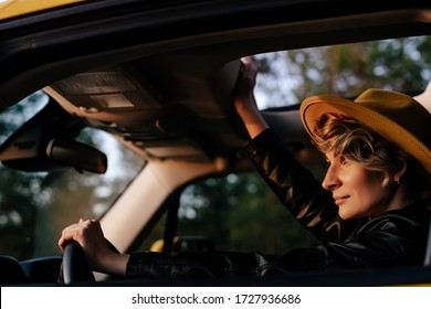 Beautiful Woman Driving Car Side View Portrait. Gorgeous Stylish Blonde Female Sitting at Wheel Watching Sunset Road. Carefree Caucasian Girl Enjoying Comfortable Auto Journey with Open Sunroof