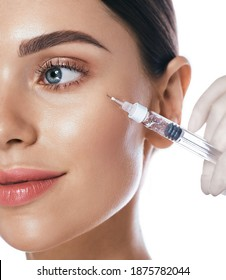 Beautiful woman during facial mesotherapy for smoothing of mimic wrinkles around eyes. Beautician doing anti-aging injection for rejuvenation and lift skin