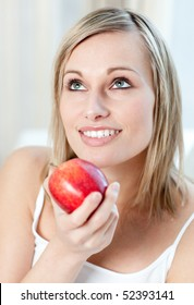 Beautiful woman eating an apple at home
