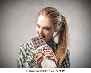 beautiful woman is eating a chocolate bar