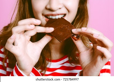 Beautiful woman eating dark chocolate on pink background