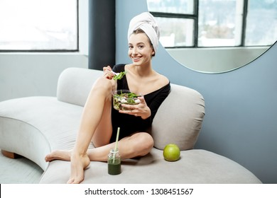 Beautiful woman eating healthy green food, relaxing after the spa procedures on the couch at home. Healthy lifestyle and self-care concept