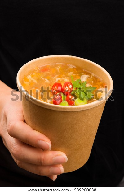 Beautiful woman eating on the go. Hot and sour soup in takeaway cup. Traditional asian cousine.