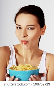 Beautiful woman eating pasta from a bowl.