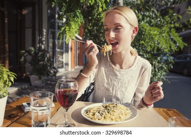 beautiful woman is eating pasta and drinking wine in the italian restaurant