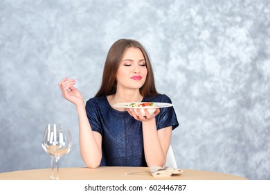 Beautiful woman eating pasta on table against light background