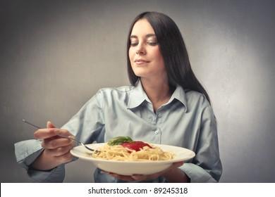 Beautiful woman eating a plate of spaghetti