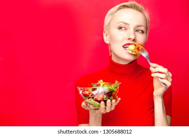 Beautiful woman eating salad wearing red dress and red lisptick over red background. Holiday, valentine day party concept