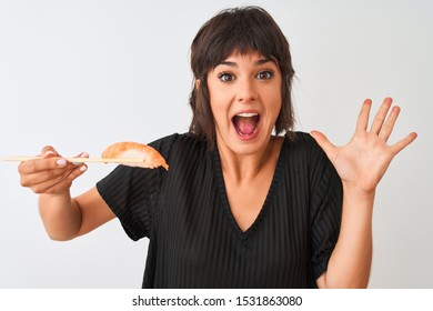 Beautiful woman eating salmon nigiri sushi using chopsticks over isolated white background very happy and excited, winner expression celebrating victory screaming with big smile and raised hands