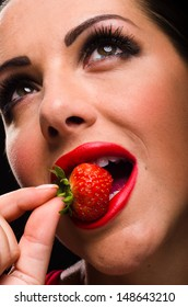 Beautiful woman eating a strawberry