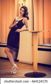 beautiful woman in elegant black dress standing on a table
