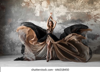 Beautiful woman in elegant dress waving on wind. Flying and fluttering dress over gray background. Fashion.