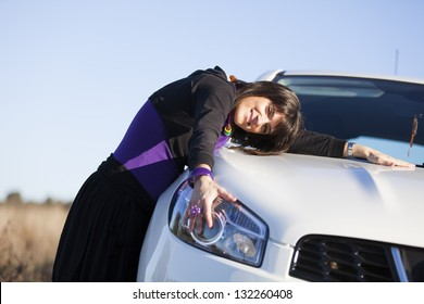 Beautiful woman embracing her new car