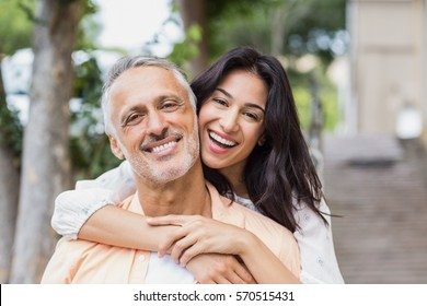 Beautiful woman embracing man from behind in city