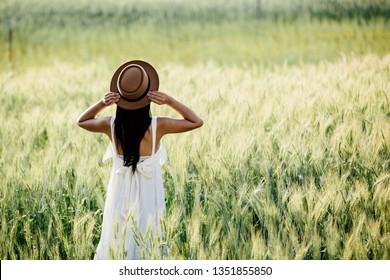 Beautiful woman enjoying in barley fields.