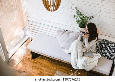 Beautiful woman enjoying cup of tea in her cosy house