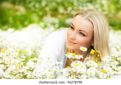 Beautiful woman enjoying daisy field, nice female lying down in the meadow of flowers, pretty girl relaxing outdoor, having fun, happy young lady and spring green nature, harmony & freedom concept