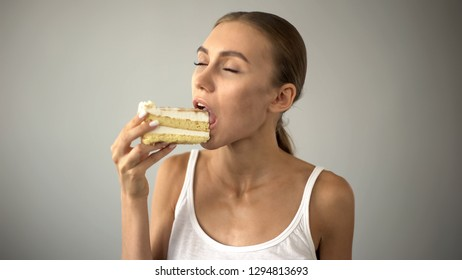 Beautiful woman enjoying delicious cake, sugar temptation, diabetes risk