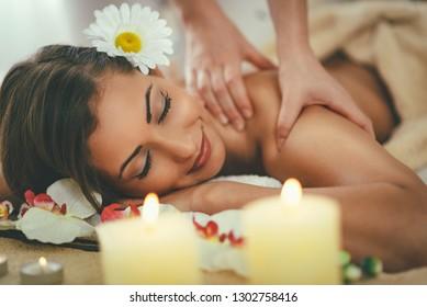 Beautiful woman enjoying during a shoulder massage at a spa.