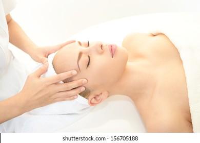 Beautiful woman enjoying facial massage in a spa center