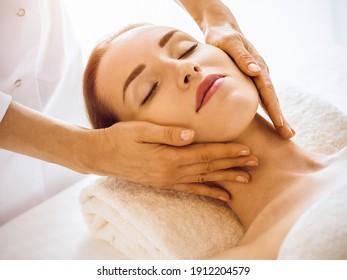 Schöne Frau, die Gesichtsmassage mit geschlossenen Augen genießt im sonnigen Wellnesscenter