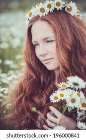 Beautiful woman enjoying field, pretty girl with freckles relaxing outdoor, having fun, holding plant, happy young lady and spring green nature, harmony concept