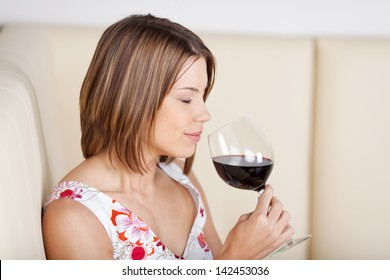 Beautiful woman enjoying a glass of red wine smelling the bouquet with her eyes closed