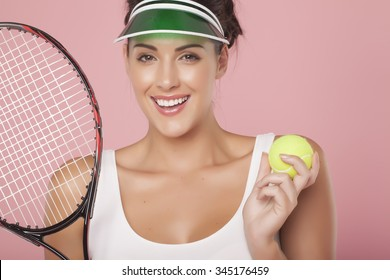 A beautiful woman enjoying the great game of tennis on a pink background. Playing tennis.