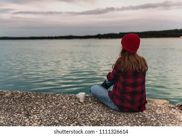Beautiful woman enjoying her day in the lake with a mug of hot coffee