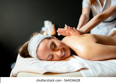 Beautiful woman enjoying massage treatment given by therapist