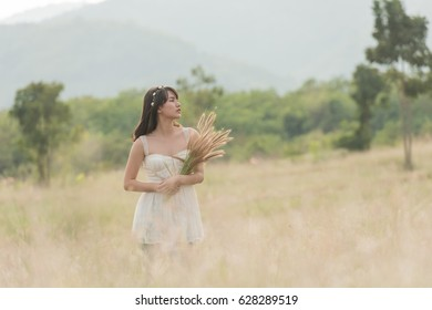 Beautiful woman enjoying meadow field, nice female lying down in meadow of flowers, pretty girl relaxing outdoor, having fun, holding plant, happy young lady and spring green nature, harmony concept