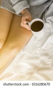 Beautiful woman enjoying morning coffee in bed