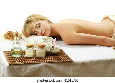 A beautiful woman enjoying spa treatment is lying on a towel over white