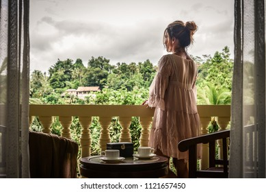 Beautiful woman enjoying the view from the balcony on jungle at Bali