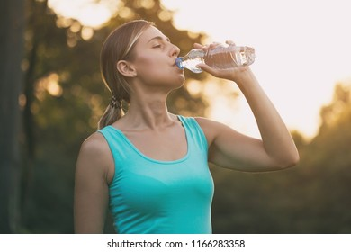 Beautiful woman enjoys drinking water during exercise.Image is intentionally toned.