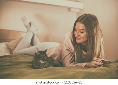 Beautiful woman enjoys resting with her cat at her home.Image is intentionally toned.
