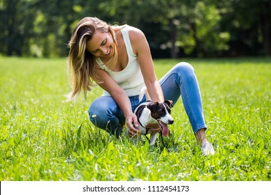Beautiful woman enjoys spending time in the nature with her cute dog Jack Russell Terrier.