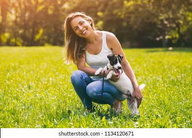 Beautiful woman enjoys spending time in the nature with her cute dog Jack Russell Terrier.Image is intentionally toned.