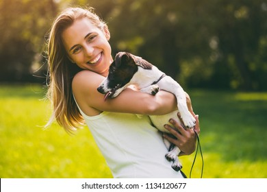 Beautiful woman enjoys spending time in the nature with her cute dog,Jack Russell Terrier.Image is intentionally toned.