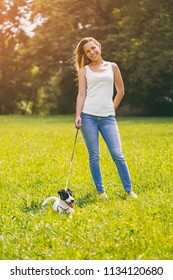 Beautiful woman enjoys spending time with her  cute dog Jack Russell Terrier in the nature.Image is intentionally toned.